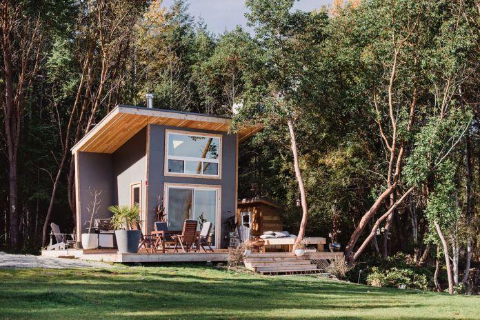 Серый крошечный дом с широкими палубами и нависающей крышей расположен посреди леса.