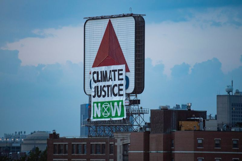 """A protest banner with the words """"Climate Justice Now"""" placed in front of the Citgo sign in Kenmore Square in Massachusetts."""