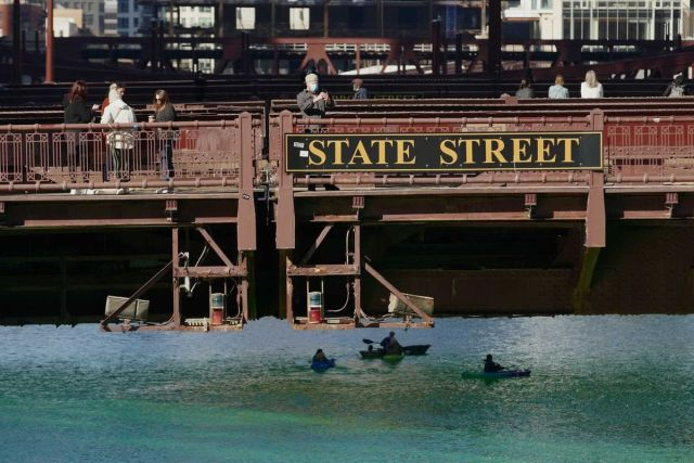 Kayakers slice through a green Chicago River March 13, 2021.