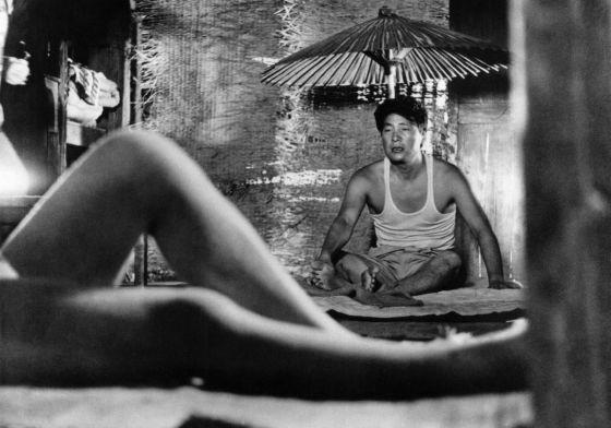 Niki Junpei (Eiji Okada) menatap seorang wanita telanjang di luar layar di Woman in the Dunes
