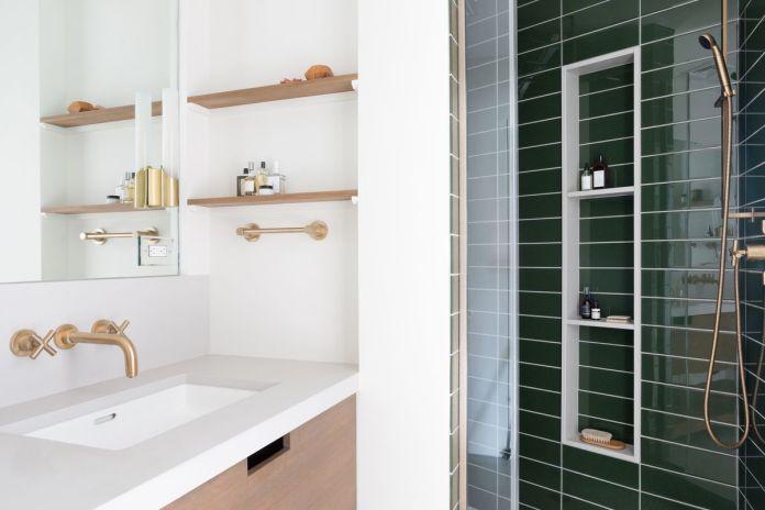 Современная ванная комната с белой раковиной, латунной сантехникой и соседним душем выложена зеленой плиткой.