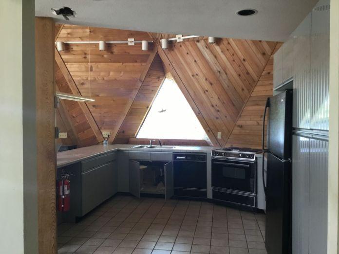 Деревянные панели покрывают кухню, которая также имеет старую бытовую технику, отслеживаемое освещение и коричневую плитку.