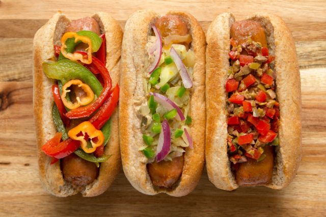 A trio of three vegan sausages in buns from Beyond Meat, topped with peppers, onions, and relish.