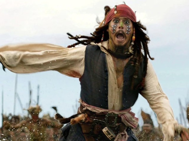 """Johnny Depp as Captain Jack Sparrow in a """"Pirates of the Caribbean"""" movie running toward the camera and yelling."""