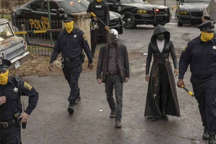 in Watchmen, vigilantes Looking Glass (Tim Blake Nelson) and Sister Night (Regina King) walk into a crime scene flanked by masked police officers