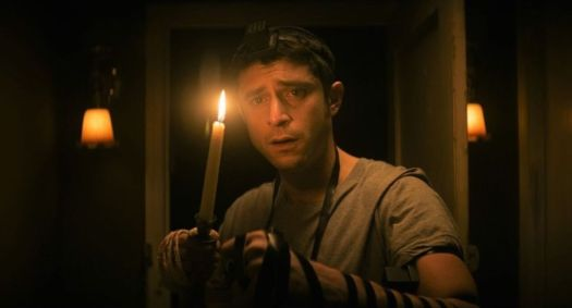 Dave Davis as Yakov holds a candle in a dark hallway in Keith Thomas' The Vigil.