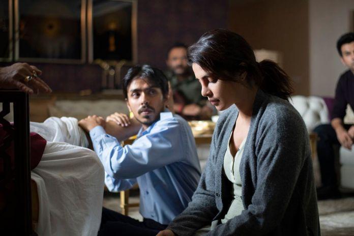Adarsh Gourav and Priyanka Chopra Jonas sit on the floor together in Netflix's THE WHITE TIGER