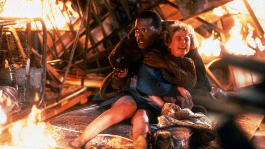 Candyman (Tony Todd) clutching Helen Lyne (Virginia Madsen) amid the burning wreckage of a bonfire in Candyman (1992)