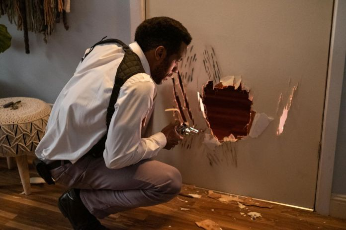 Nate (McKinley Freeman) examines scratch marks and a hole in a door