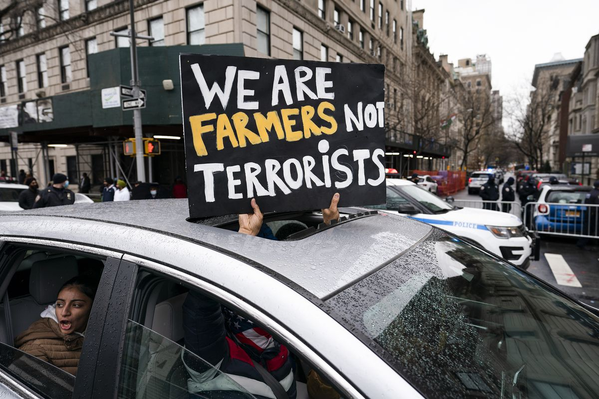 "A protester holds a sign out the sunroof of a car that reads, ""We are farmers not terrorists."""