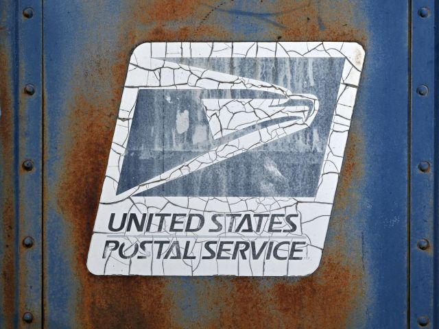 The logo on the side of a USPS collection box, which is rusty and weathered.