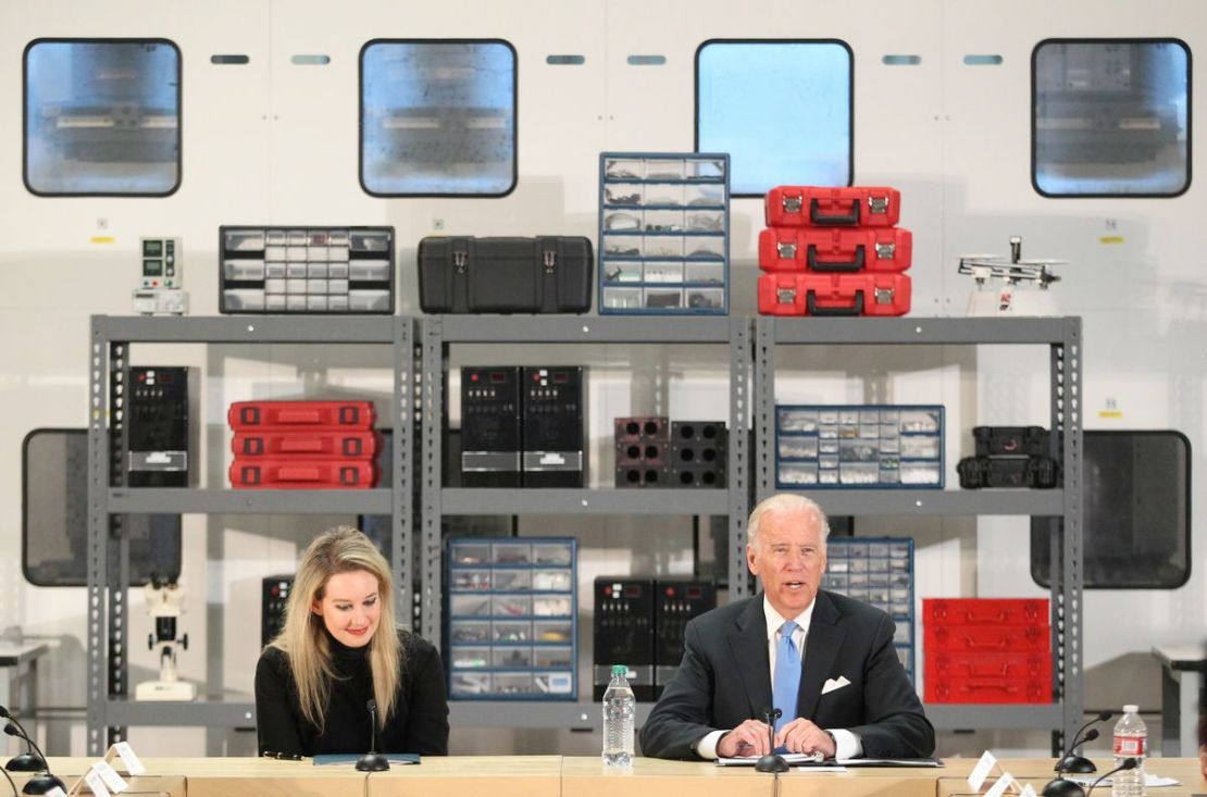 Elizabeth Holmes sitting next to Joe Biden in front of shelves of scientific-looking hardware.