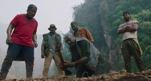 a group of men look at an excavation site