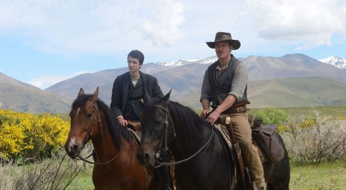 Jay (Smit-McPhee) and Silas (Fassbender) ride horses side by side.