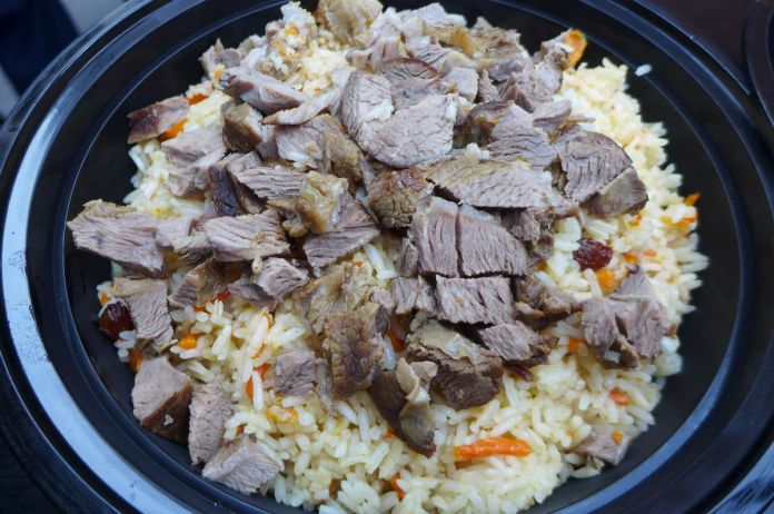 Rice and carrots with small pieces of lamb on top.