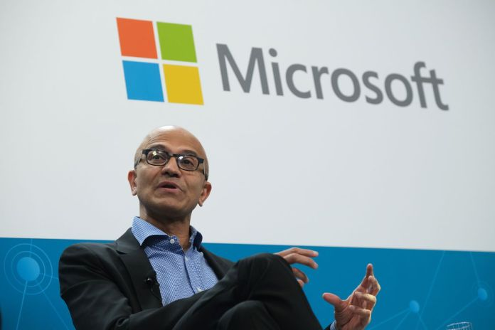 Satya Nadella, CEO of Microsoft, sitting on stage with a Microsoft logo behind him