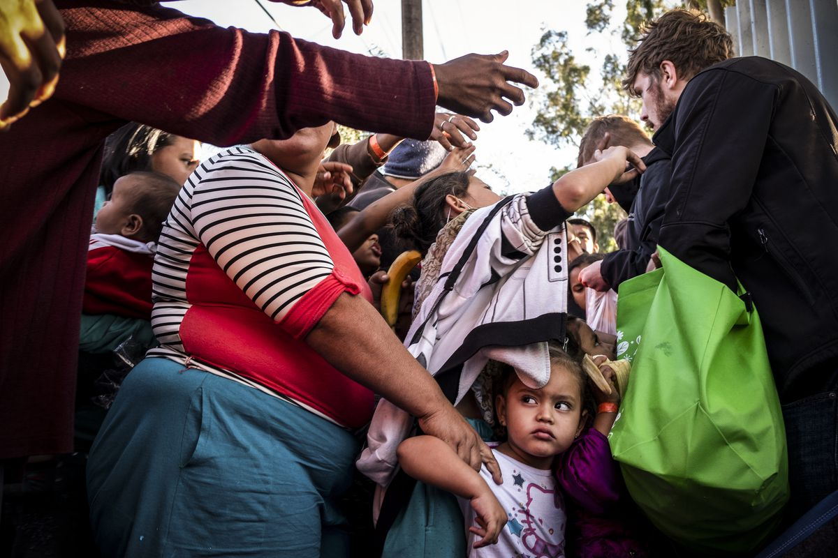 A group of Central American migrants wanting to reach the US, wait in line for fruit given by volunteers outside a temporary shelter in Tijuana near the US-Mexico border fence, on November 23, 2018.
