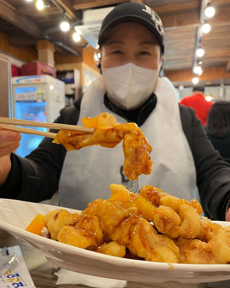 Woman in a mask holds up chopsticks with food in it.