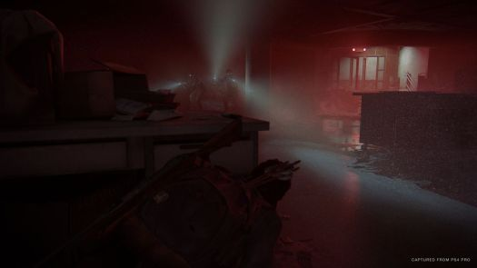 Ellie crouches behind a desk, hiding from a group of enemies in a room lit only by their flashlights and the red glow of an exit sign in The Last of Us Part 2