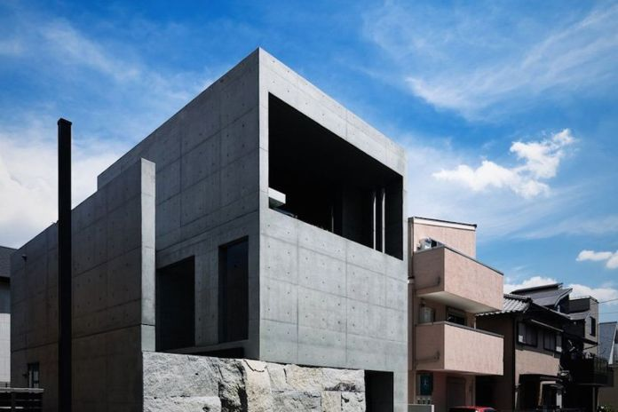 Квадратный бетонный дом покоится на каменном основании.