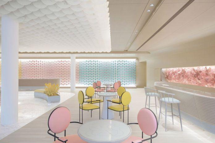 В кафе установлены розовые и желтые стулья на кремовом фоне.