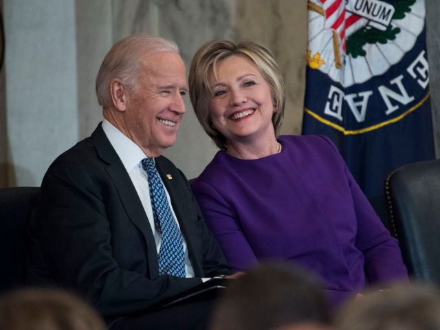 Joe Biden and Hillary Clinton sit and smile as they attend a ceremony in the Russell Building's Kennedy Caucus Room, December 8, 2016.