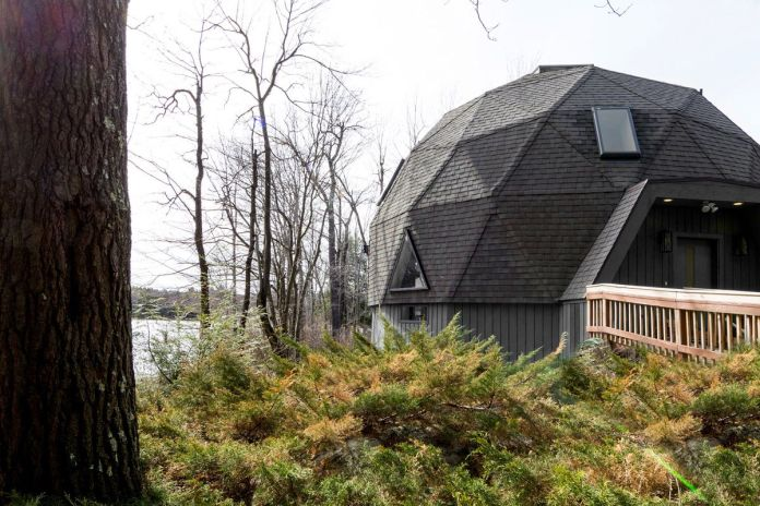 Геодезический купол дома окружен зеленью и озером.