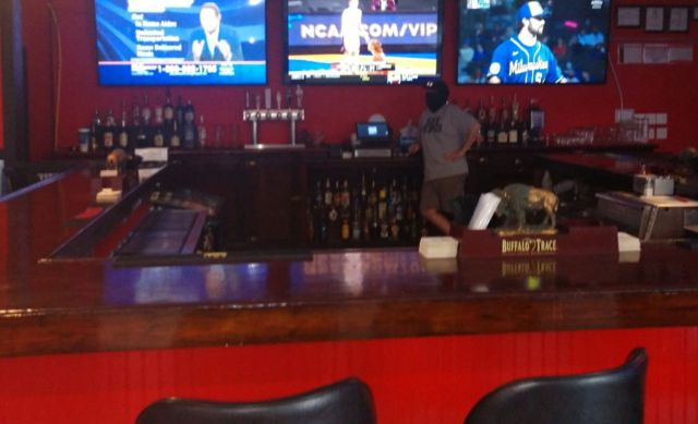 A bartender tends bar at the Embarras bar in Villa Grove, Ill., on Tuesday.