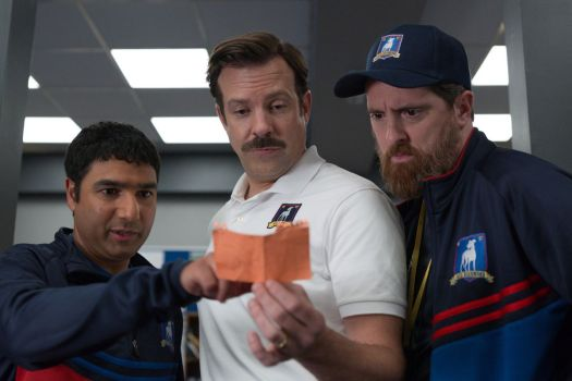 Ted Lasso and his assistant coaches lean over a note