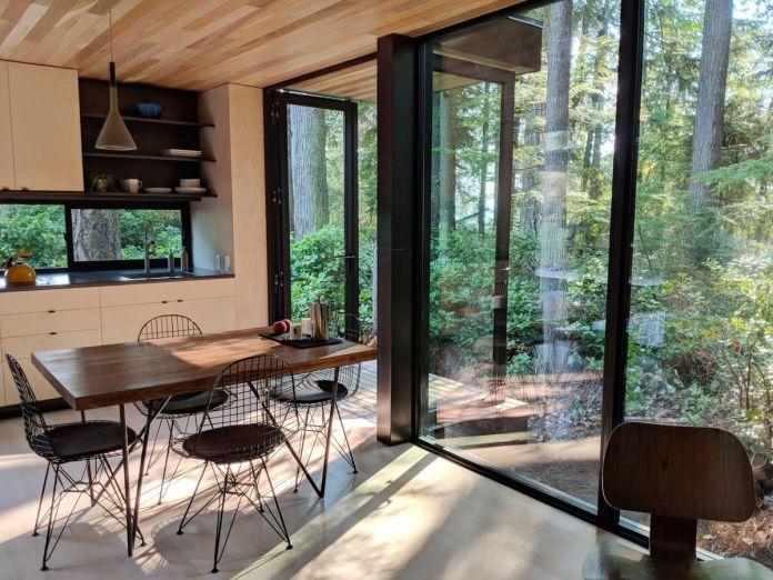 Кухня с небольшим столом, четырьмя каркасными стульями и большими окнами, которые выходят на улицу.