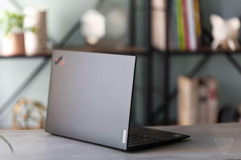 Il Lenovo ThinkPad X1 Carbon Gen 9 su un tavolo davanti a una libreria, rivolto verso la fotocamera, inclinato a destra.