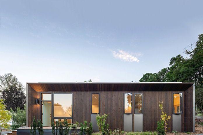 Компактный прямоугольный деревянный дом со стеклянными стенами.