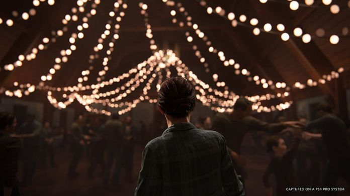 Ellie stands in front of a room strung with lights in a screenshot from The Last of Us Part 2