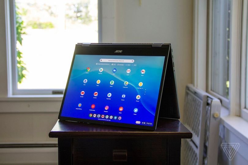 The Acer Chromebook Spin 713 in tent mode, angled slightly to the left. The screen displays a grid of Android apps on a blue background.