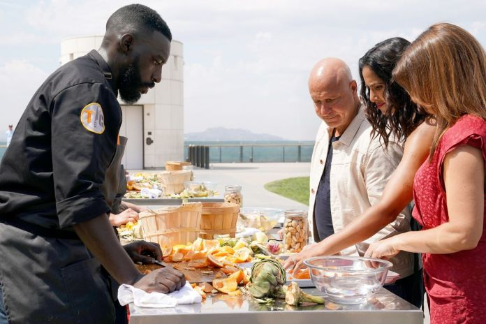 Top Chef competitor Eric Adjepong stands in front of an outdoor table covered with wooden baskets, chopped fruit, nuts, and artichokes, as judges Tom Colicchio, Padma Lakshmi, and Gail Simmons examine his work.