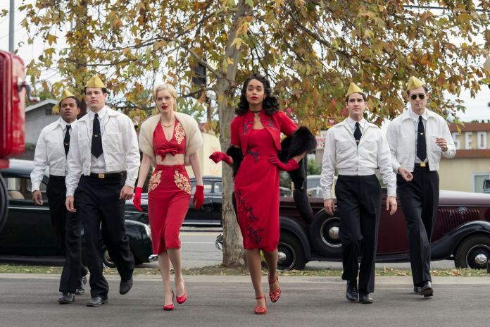 A white woman and a black woman in form-fitting red outfits cross a parking lot, in front of four men in white jackets, black ties, and peaked khaki garrison hats.