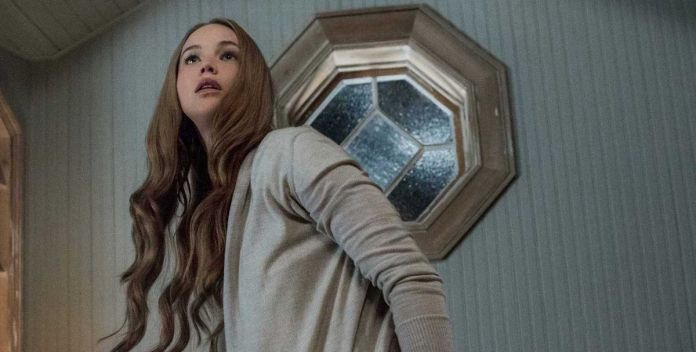 Jennifer Lawrence stands in front of an octagonal window and looks worried in Mother!