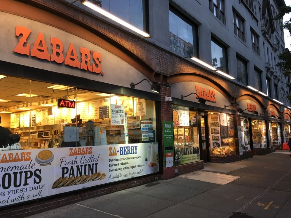 The exterior of deli and grocery store Zabar's, orange sign illuminated, on the Upper West Side of Manhattan at dusk.