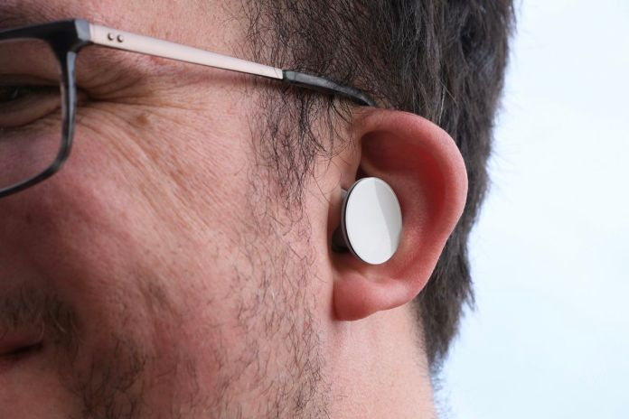 The Surface Earbuds pictured worn in the reviewer's left ear.