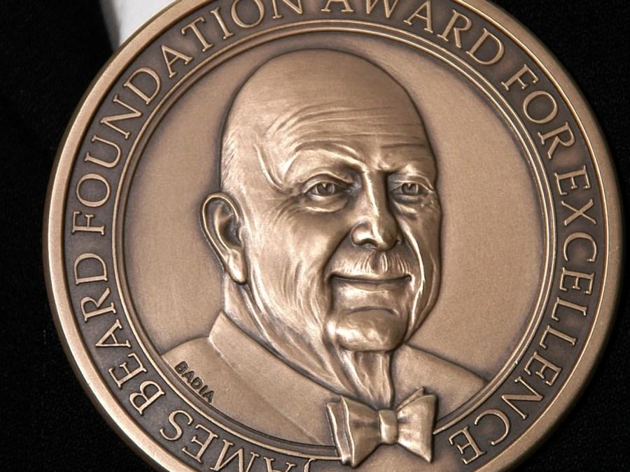 A photo shows a bronze James Beard Award medal against a black background.