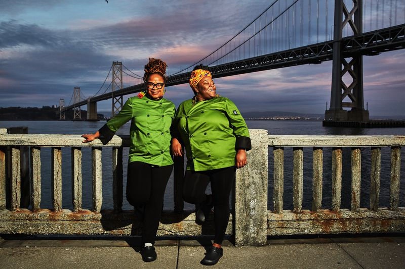 Two women in green chef coats stand in front of a river with a suspension bridge in the background