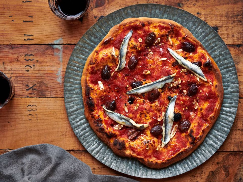 A pizza topped with tomato sauce, white anchovies, and olives sits on a wooden table with two glasses of red wine and a grey napkin.