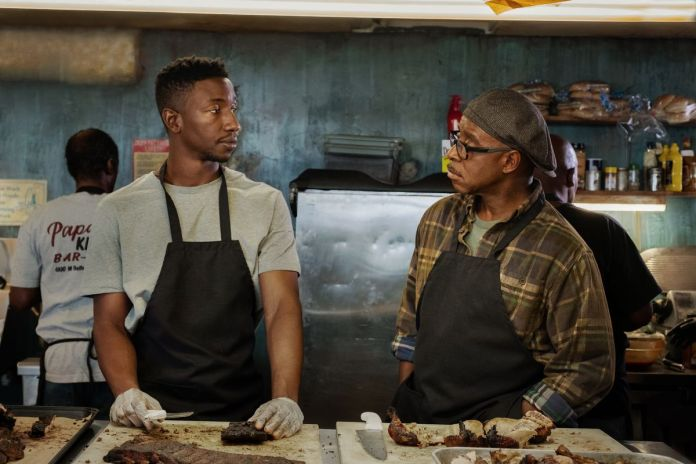 two men stand over a counter of barbecue