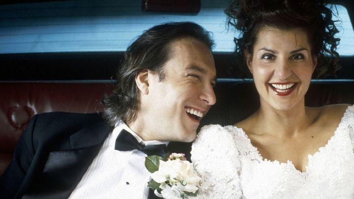 Ian (John Corbett) and Toula (Nia Vardalos) laugh in the backseat of a car in a screenshot from My Big Fat Greek Wedding