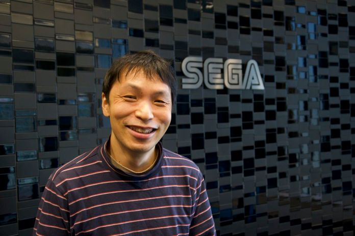 Hideaki Kobayashi stands in front of the Sega logo on a wall