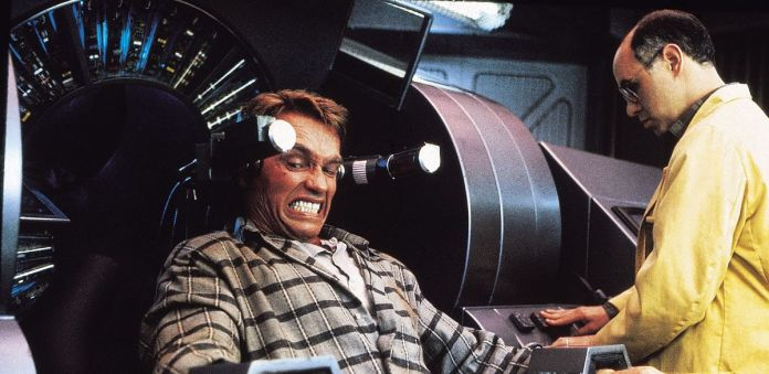 Arnold Schwarzenegger grimaces as memories are implanted in his head — or not?!? — in Total Recall.