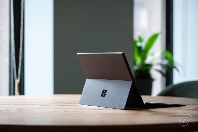 Il Surface Pro 8 su un tavolo visto da dietro a destra, aperto, con la Signature Keyboard attaccata e il cavalletto fuori.  Sullo sfondo c'è un muro verde e una pianta in vaso.