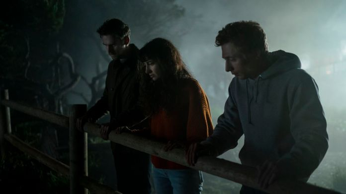 Dan Stevens, SheilaVand, and Jeremy Allen White look over a fence in a misty scene in Dave Franco's The Rental.