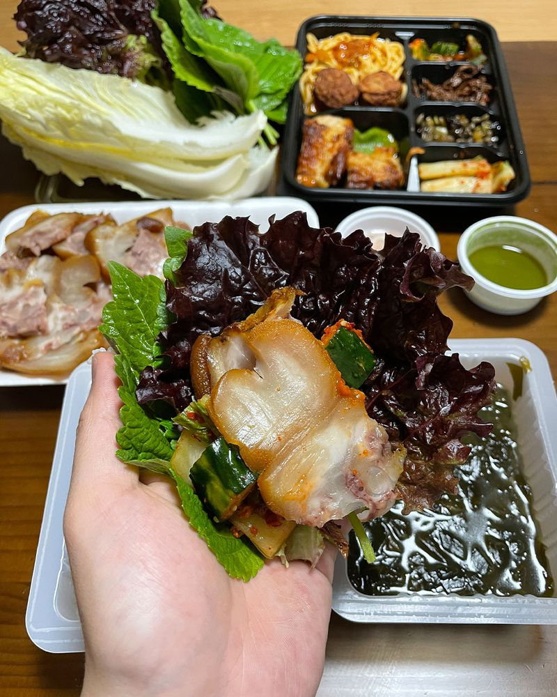 A hand holds leaves with pieces of pork inside.