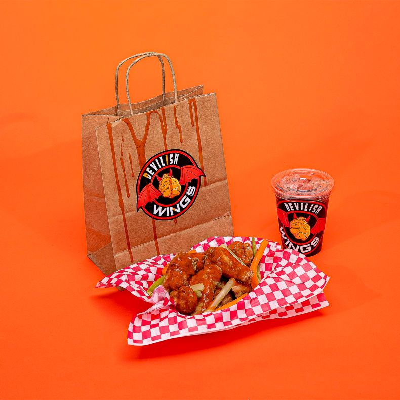 A bag with a sticker for a fake brand called Devilish Wings next to a basket of chicken wings and a clear plastic cup with another sticker for Devilish Wings on an orange backdrop.